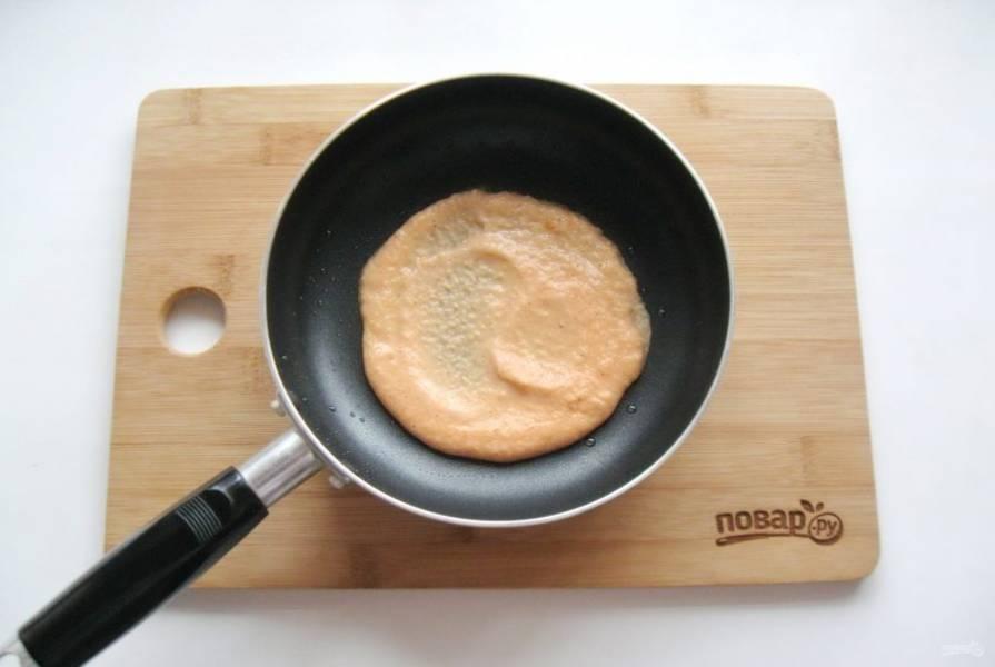 Выложите две столовые ложки теста. Круговыми движениями разровняйте его по сковороде. Диаметр блина должен быть 11-12 см. Обжаривайте блин с одной стороны 1,5 минуты, пока поверхность блина не станет матовой и не подсохнет.