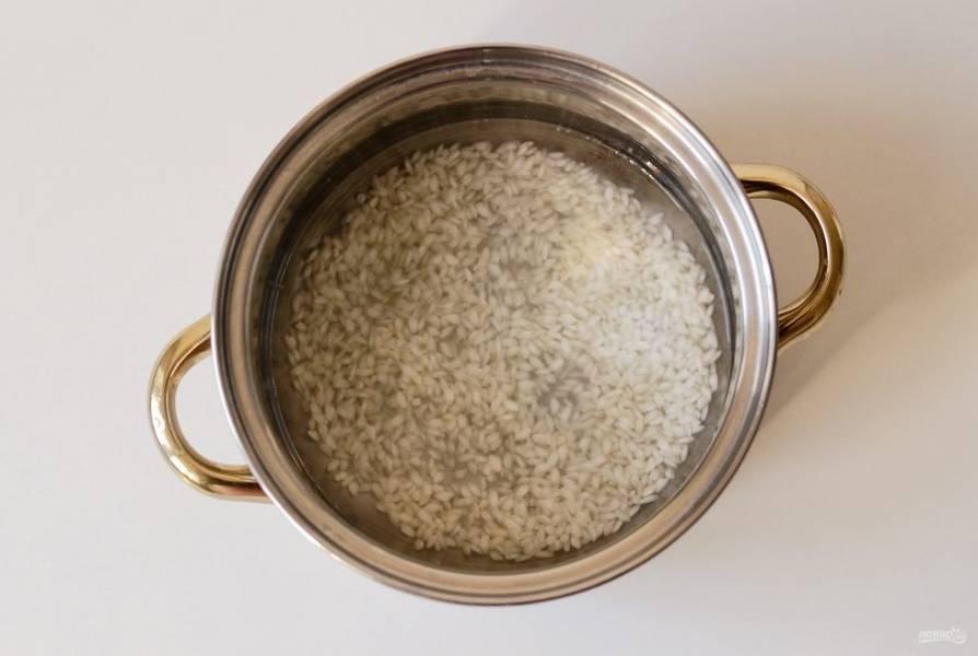 Рис промойте в холодной воде до прозрачности. Переложите в кастрюлю, залейте водой. Добавьте сахар и ванилин. Варите рис под крышкой на маленьком огне до полной готовности. Это займет примерно 20 минут.