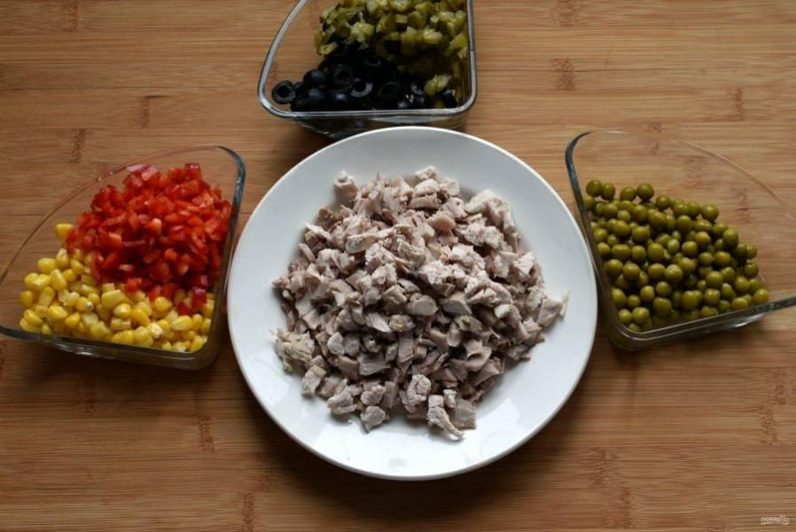 Готовую курицу выньте из бульона, охладите, снимите кожу, удалите кости и нарежьте мясо мелкими кубиками. Так же мелко нашинкуйте маринованные огурцы и перец, маслины нарежьте колечками, а горошек и кукурузу хорошо отцедите от заливки.