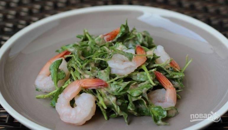 Выложите заправленный салат в блюдо. Отварите сырые коктейльные креветки (минуты 3). Затем остудите их и очистите от панциря. Выложите креветки на салат.