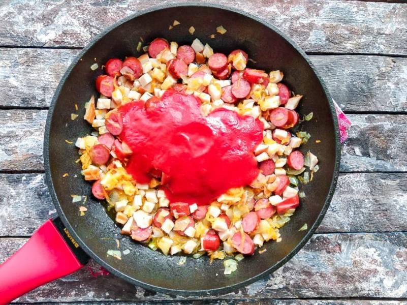 Добавьте 2 столовые ложки томатной пасты, перемешайте все ингредиенты и тушите в течение 5-6 минут.