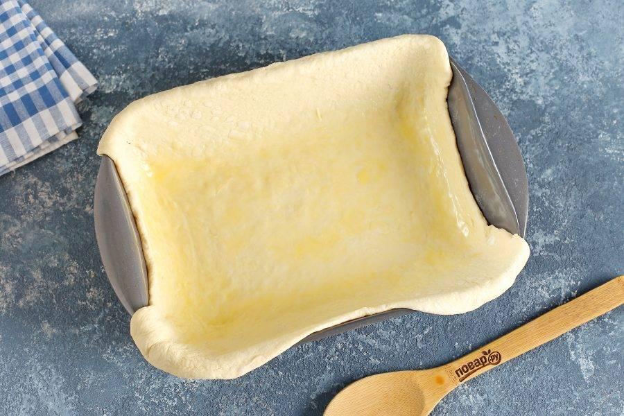 Одну половину теста раскатайте и выложите в жаропрочную форму, смазанную маслом. Тесто должно быть больше, чем форма для запекания и концы должны немного свисать. Смажьте тесто растопленным сливочным маслом.