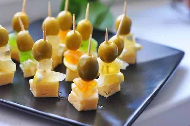 4. Теперь на сыр выкладываем дольку лимона, сахарим, а сверху - оливку. И все накалываем на шпажку. Выкладываем канапе на большое блюдо, подаем как закуску к мартини.