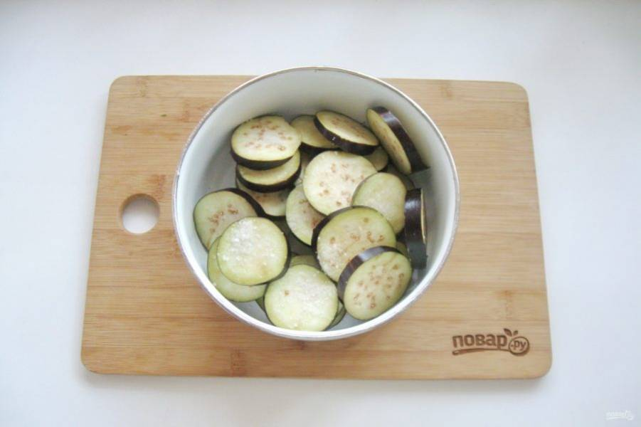 Выложите нарезанные баклажаны в миску, посыпьте солью и перемешайте. Дайте постоять 15 минут, после жидкость слейте.