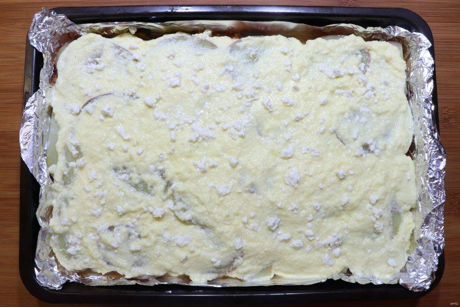 Дно формы для выпечки смажьте растительным маслом и выложите баклажаны одним слоем. Слегка посолите и поперчите. Поверх баклажанов нужно распределить фарш. Следующим слоем будет картофель. Сверху равномерно распределите соус, посыпьте фетой.