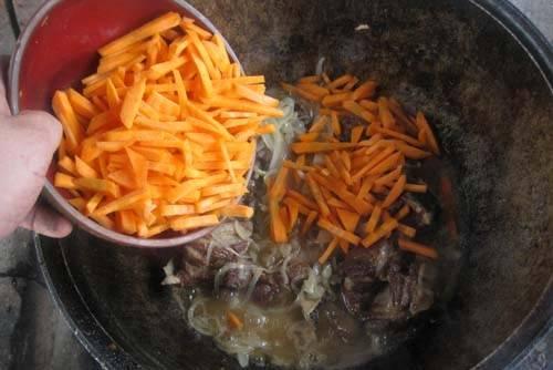 Добавьте в казан к мясу морковь и лук. Перемешайте.