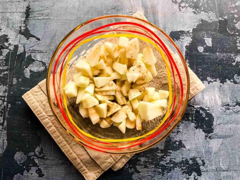 Яблоки очистите от кожуры, удалите сердцевину, мелко нарежьте и смешайте их с корицей.