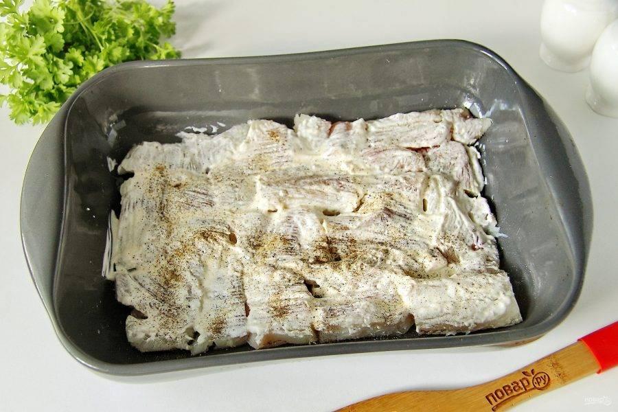 Смажьте рыбу сметаной, посыпьте солью и молотым перцем. Если блюдо готовите для детей, то перец исключите.