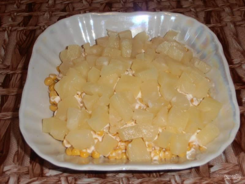 Консервированные ананасы нарезаем кубиками и выкладываем следующим слоем.
