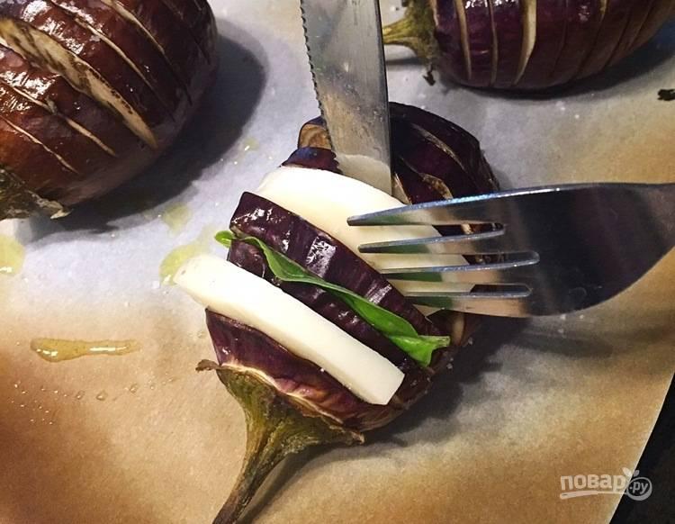 4. В каждую щелочку баклажана положите ломтик сыра и листочек базилика.