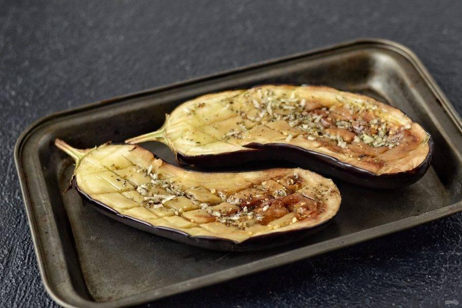 Вытащите баклажаны из духовки. Переложите их в форму для запекания, смажьте ароматным маслом с травами и запекайте ещё 10 минут.