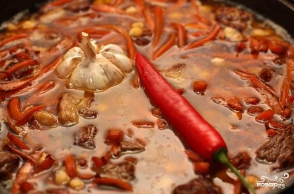 7. Влейте воду, предварительно растворив в ней соль. Поместите сверху вымытую головку чеснока и перец чили (используйте в рецепт приготовления узбекского плова с нутом молотый черный перец, если не любите слишком острое).
