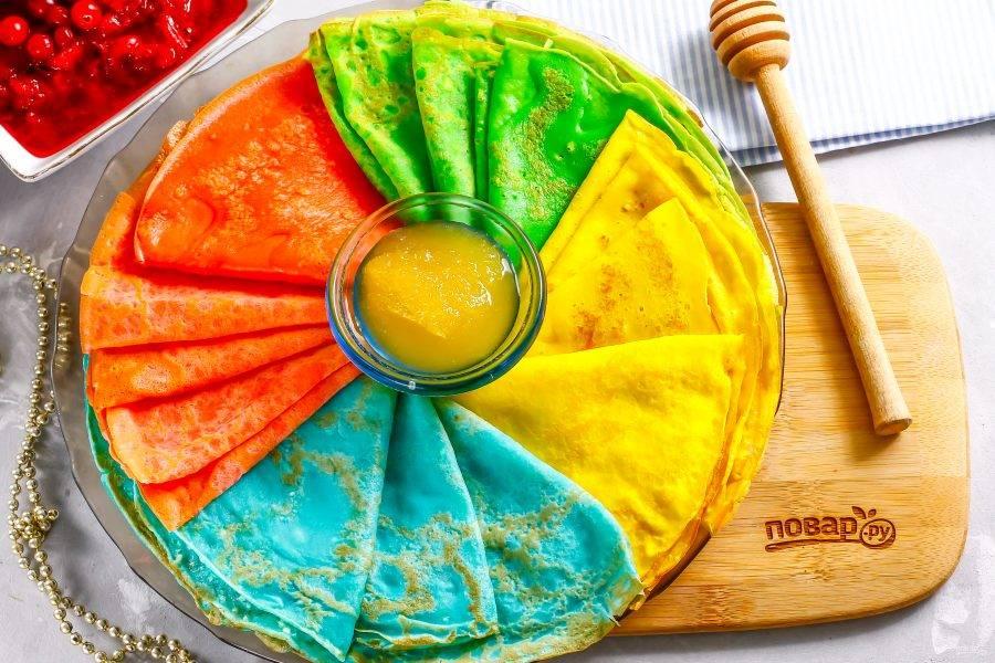 На середину тарелки разместите пиалу с медом любого сорта или с джемом. Подайте вкусные разноцветные блины к столу.