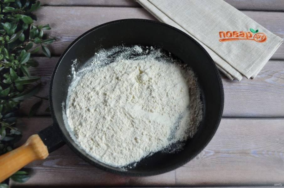 3. Всыпьте в сковороду пшеничную муку, помешивая ложкой, жарьте до кремового цвета.