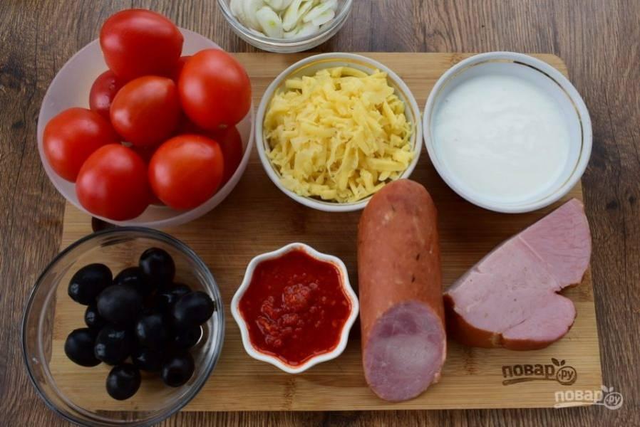 Помидоры вымойте, обсушите. С колбасы снимите защитную оболочку. Сыр натрите на крупной терке. Лук очистите, нарежьте тонкими слайсами.