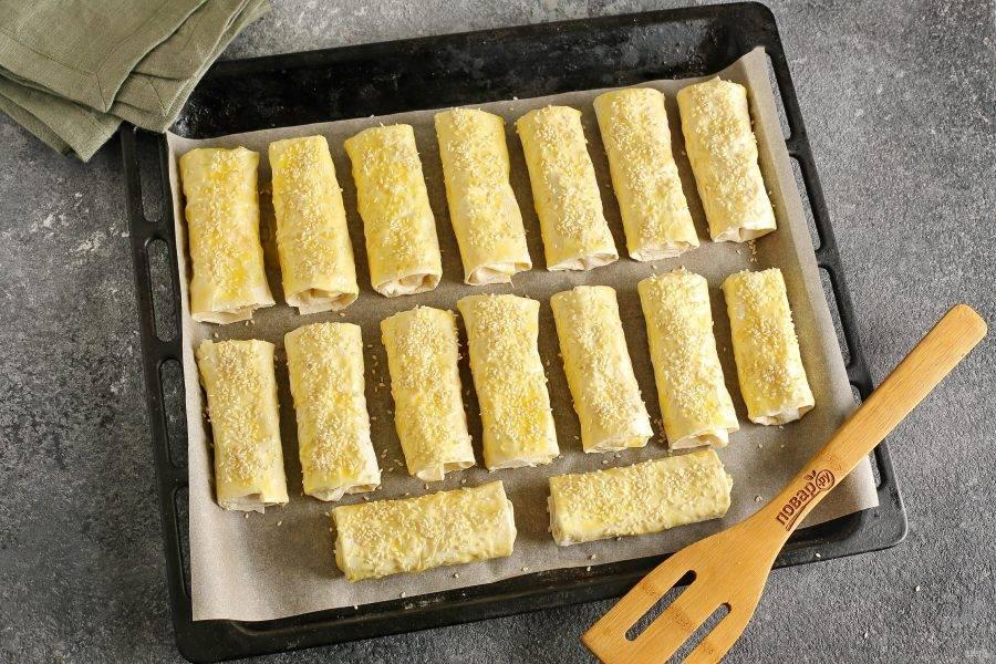 Переложите заготовки на противень, смажьте желтком и посыпьте кунжутом. Запекайте в духовке при температуре 180 градусов около 20 минут (до золотистого цвета).