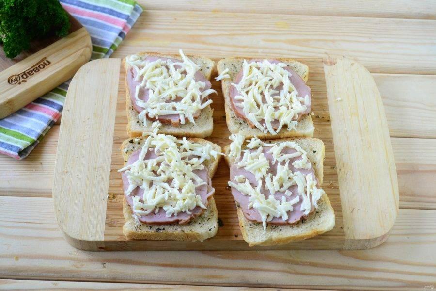 Затем на каждый ломтик хлеба положите по ломтику ветчины и примерно по 1 ч. ложке натертой на крупной терке моцареллы.