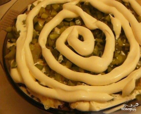5.Приступите к формированию салата. Уложите первым слоем половину печени. Смажьте её майонезом. Сверху выложите половину от общего количества жареного лука.