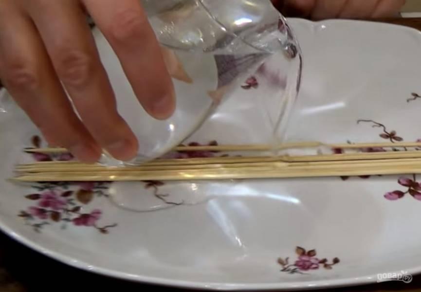 1. Деревянные шпажки замочите в холодной воде и оставьте на 30 минут. Куриное филе нарежьте на длинные полоски. Противень выстелите фольгой.