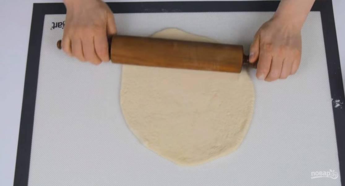 1. За 30 минут до выпекания поставьте противень в духовку и разогрейте ее до 250 градусов. Заранее приготовленное тесто для пиццы растяните на присыпанной мукой поверхности, а затем раскатайте в круг диаметром 30 см.