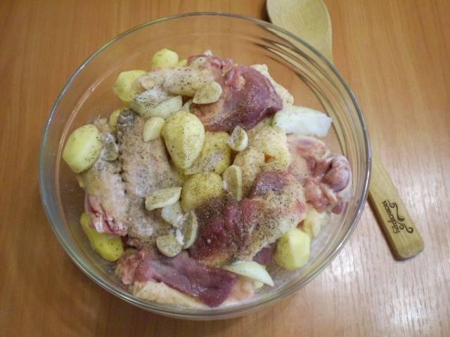 Лук и чеснок порежьте крупными дольками. В удобной глубокой таре соедините утку с очищенным картофелем, луком и чесноком. Добавьте специи и соль. Перемешайте.