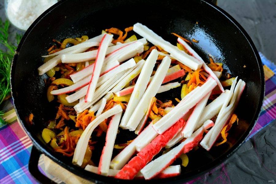 К размягченному луку и морковке добавьте крабовые палочки.