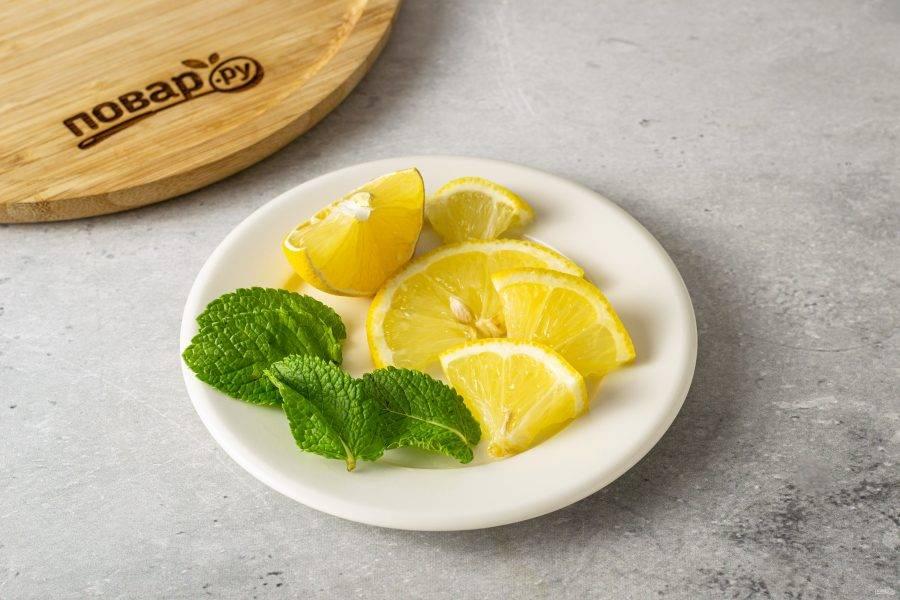 Лимон нарежьте на тонкие дольки. Отделите пару листиков мяты.