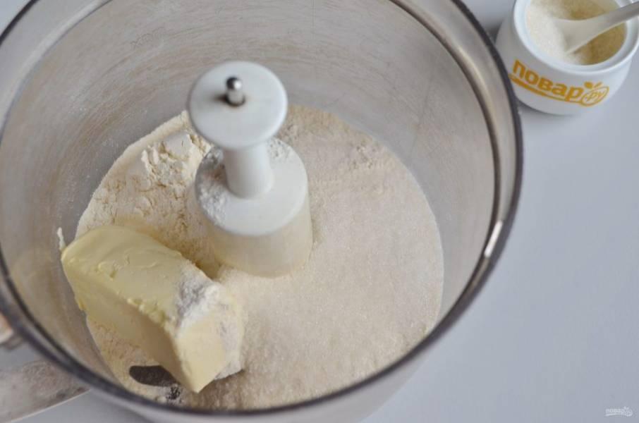 2. В чашу кухонного комбайна положите холодное масло, сахар, муку и разрыхлитель. Включите машинку на пару минут, должны образоваться масляно-мучные крошки.