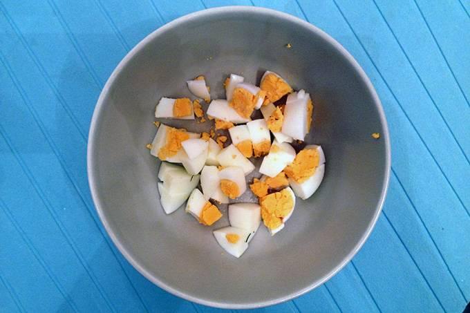 Через 5 минут солим, перчим. Варим на медленном огне еще пару минут. Затем достаем мясо и нарезаем его на маленькие кусочки, затем возвращаем обратно в кастрюлю. Пока суп томится вкрутую отвариваем яйца, очищаем их и нарезаем кубиками. Кладем на дно тарелки.
