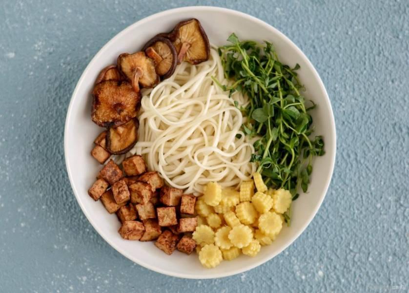 В центр тарелки выложите лапшу, а по кругу порезанную кукурузу, ростки гороха, тофу и грибы. Влейте бульон.