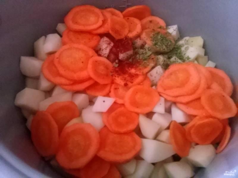 Сверху тушенки положите нарезанную картошку и морковь. Добавьте приправы, посолите по вкусу, перемешайте. Тушите при закрытой крышке.