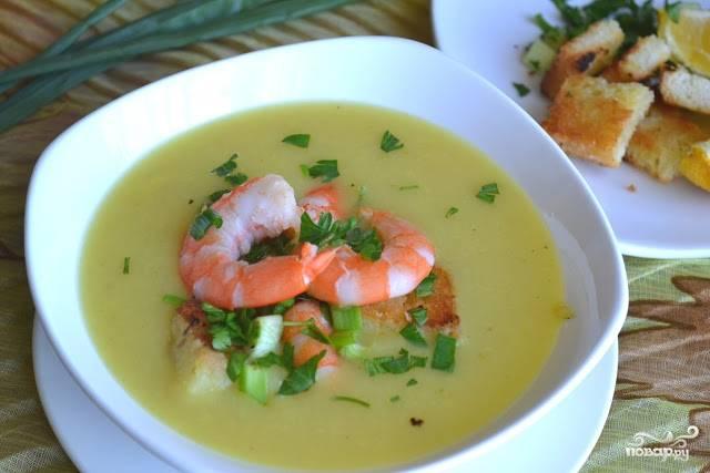 Картофельно-луковый суп разлейте по глубоким тарелкам. Сверху выложите обжаренные креветки. Чтобы украсить блюдо, нарежьте петрушку и покрошите её в тарелки. Также блюдо можно украсить чёрным молотым перцем или паприкой.