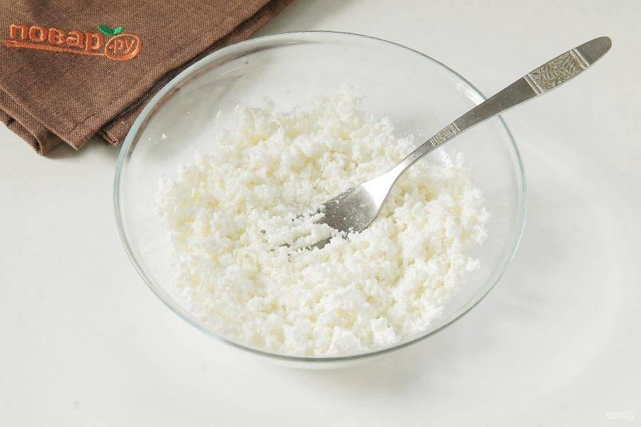 Творог разотрите вилкой с солью и сахаром.