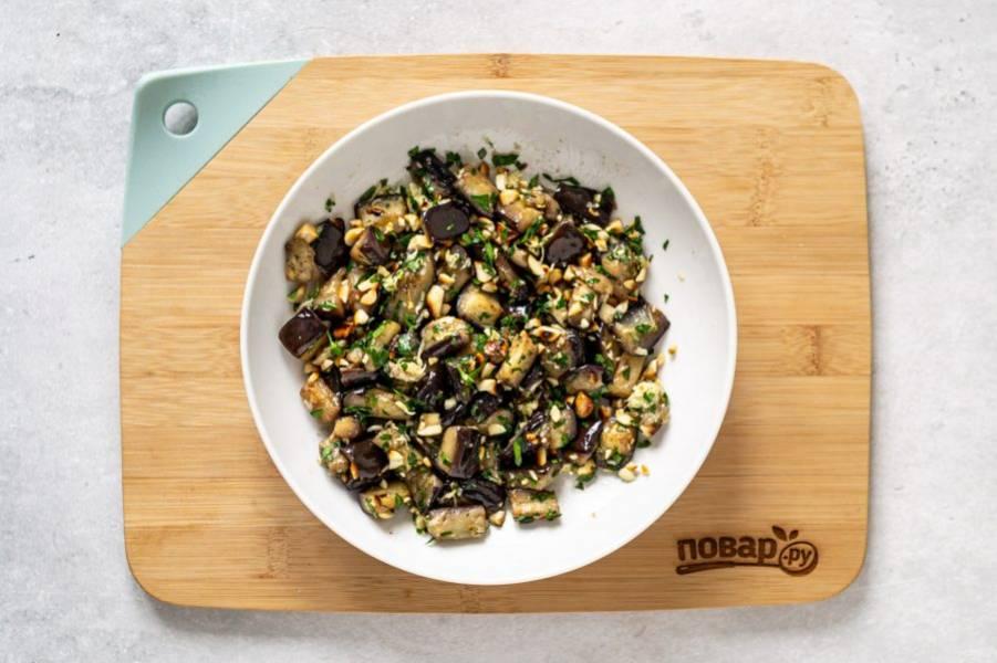 Соедините жареные баклажаны с чесноком, петрушкой и арахисом. Добавьте соль, красный и черный молотый перец, перемешайте.