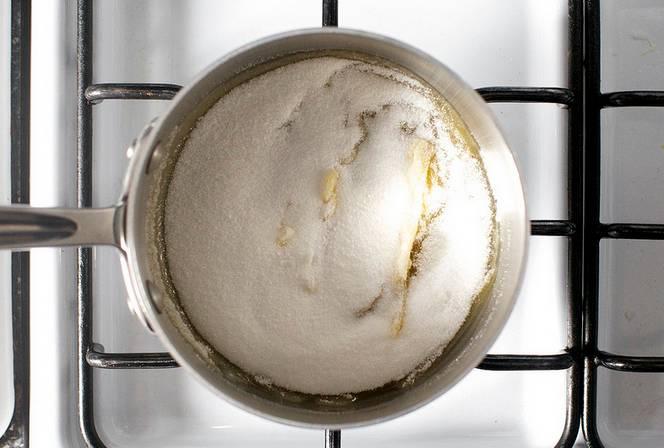 1. Начать нужно с того, что подготовить пергамент, который выложить на тарелку или поднос и смазать растительным маслом. В небольшой сотейник всыпать сахар и отправить на огонь.