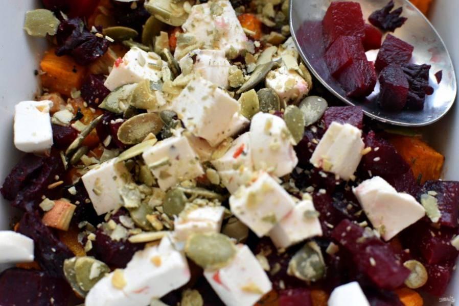 Добавьте кубики сыра, посыпьте тыквенными семечками и  свежемолотым перцем.