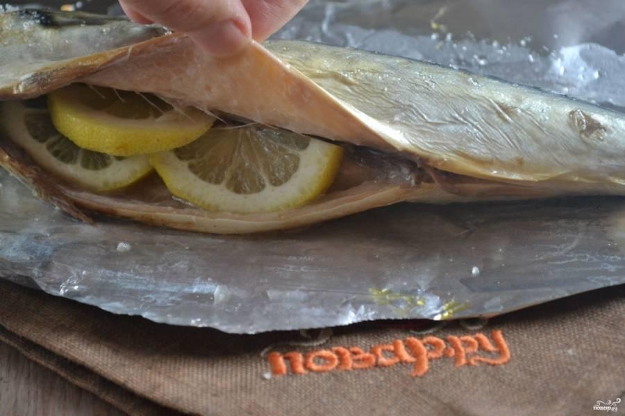 В брюшко рыбке положите 2-3 дольки лимона.