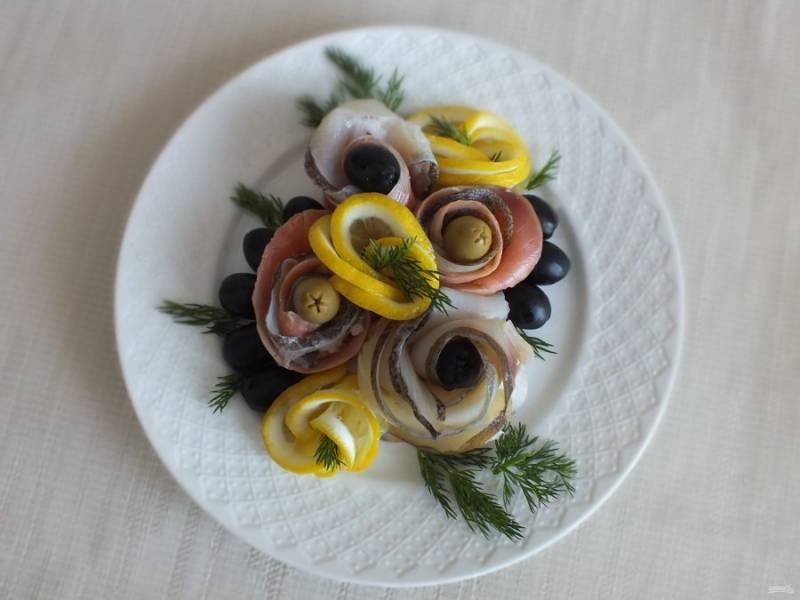 Скрутите розочки из оставшихся лимонных долек. Разложите вокруг рыбы, дополните оливками, маслинами, укропом.