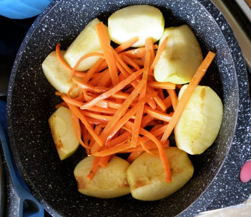 В другой сковороде разогрейте остаток масла и выложите очищенные и разрезанные на четвертинки яблоки. Выкладывать их нужно по краям сковороды. В середину положите брусочки моркови. Посыпьте все ложечкой сахара и обжарьте до золотистости.