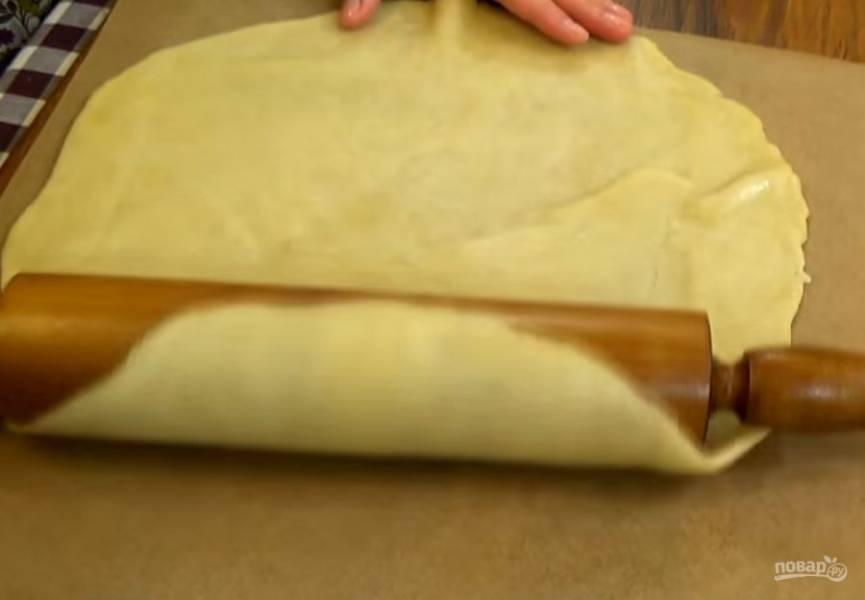 2. Яблоки нарежьте пластинками и смешайте с корицей и крахмалом. Раскатайте тесто в пласт толщиной полсантиметра. При помощи скалки перенесите на бумагу для выпечки.