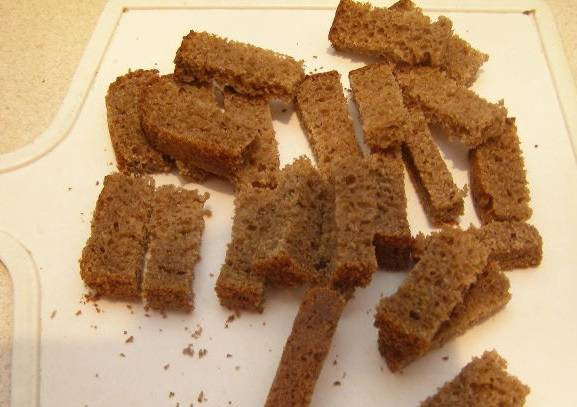 Черный хлеб режем ломтиками и подсушиваем в духовке 40 минут, температура 200 градусов.