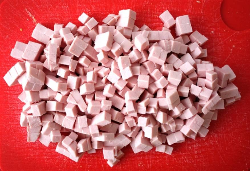 Докторскую колбасу порежьте мелкими кубиками.