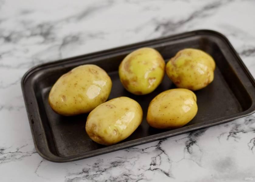 Картофель хорошо помойте и обсушите. Смажьте картофелины растительным маслом и запекайте в духовке 30-40 минут при температуре 200 градусов.