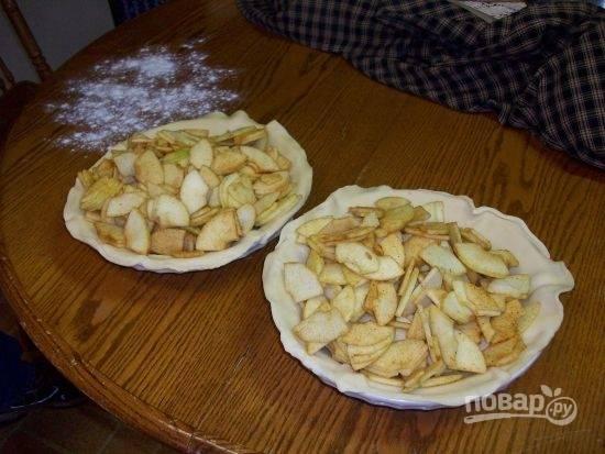 Тесто раскатайте и положите в форму для пирога. Выложите яблоки таким образом, чтобы они полностью заполнили форму до краев с небольшой горкой.