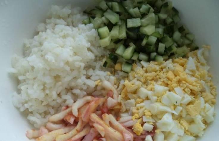 В миску выкладываем: порезанные огурцы, яйца, кальмаров и рис. Солим по вкусу.