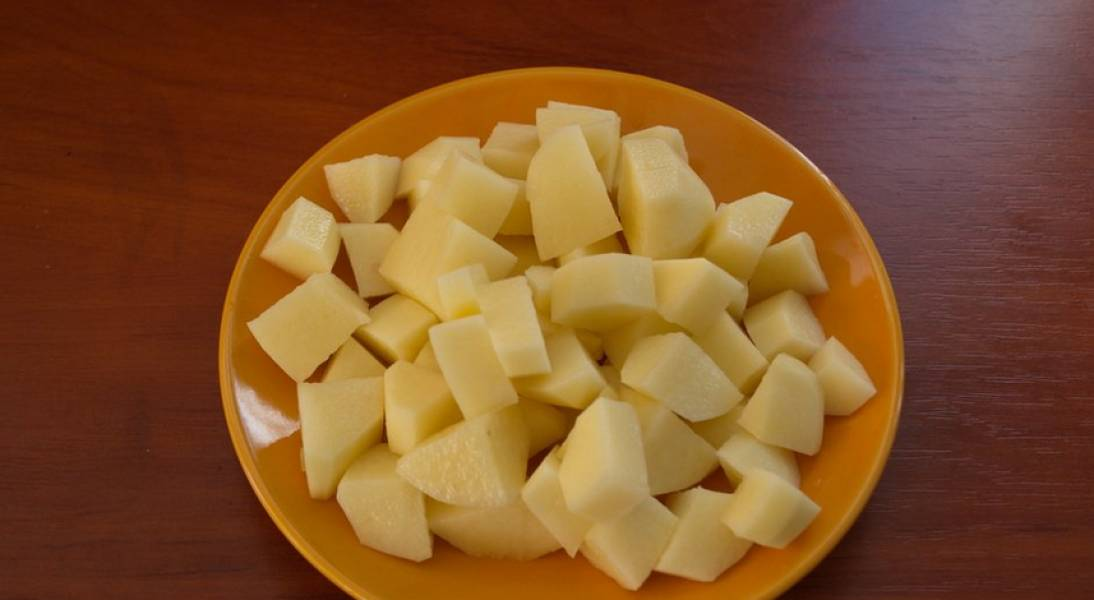 Через 25 минут добавляем к мясу картофель, порезанный кубиками.