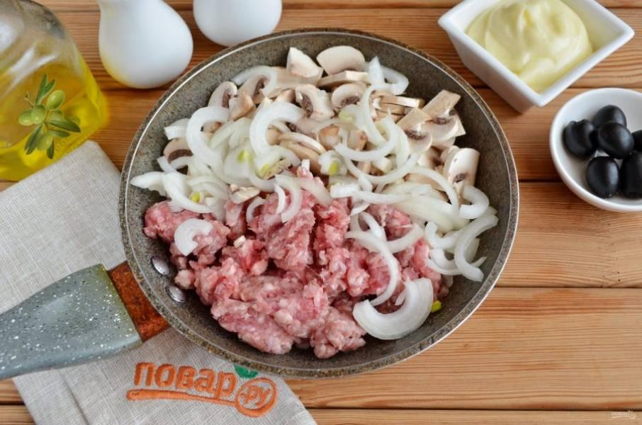 В сковороду налейте столовую ложку масла. Положите грибы, лук и фарш. Добавьте соль, в конце жарки — перец черный молотый. Жарьте на среднем огне до готовности всех ингредиентов.