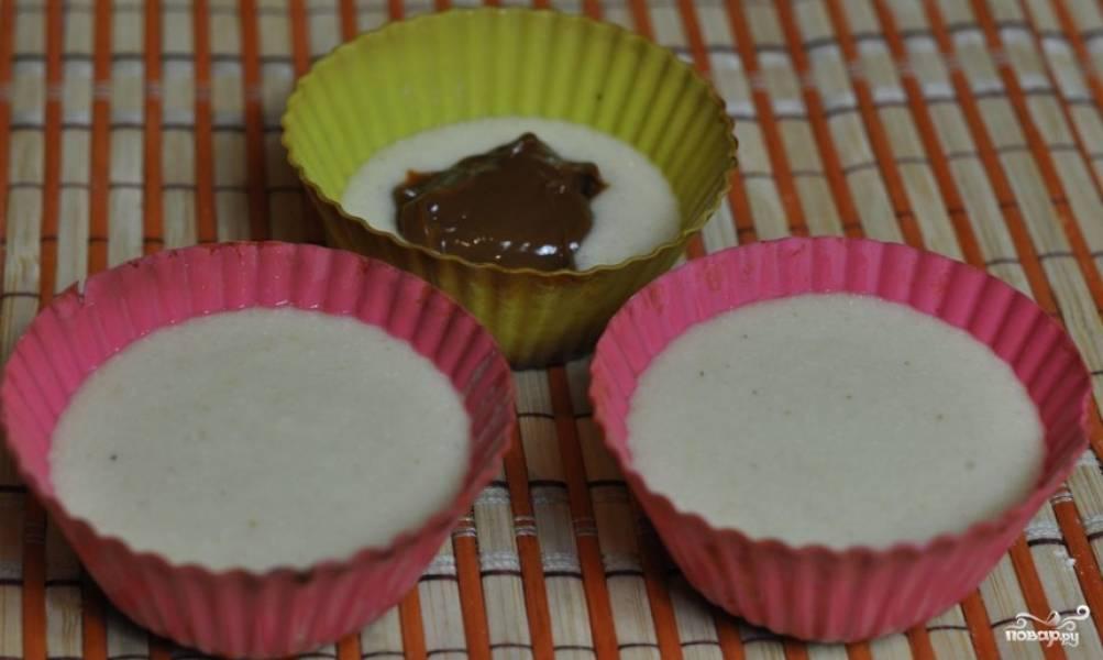 2. Влейте яично-молочно-масляную смесь в сухие ингредиенты. Все тщательно перемешайте до однородности (без комочков). Возьмите формочки и промажьте их маслом. Затем выложите 1 или 1,5 ст. ложек теста в каждую форму. Положите начинку из вареного сгущенного молока и сверху налейте небольшое количество теста, чтобы оно прикрывало начинку.