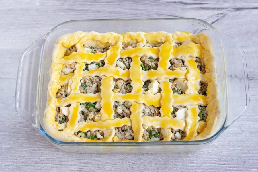 Прищипните края пирога и смажьте всю поверхность теста сырым желтком. Поставьте в разогретую до 180 градусов духовку на 25-30 минут.
