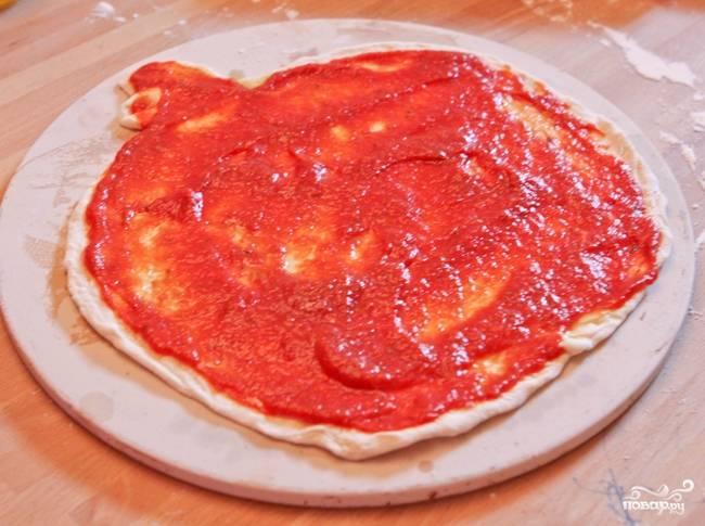 2. Смажьте основу томатным пюре.